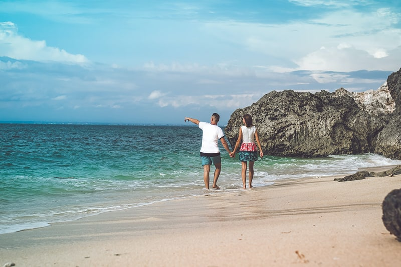 man and woman walking on seashore while holding hands