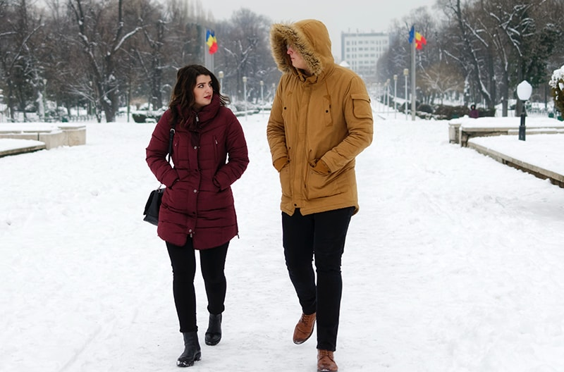 man and woman walking on the snow during daytime