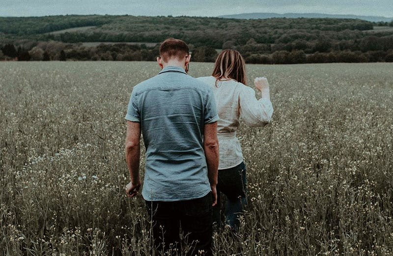 man and woman walking in the middle of the fields