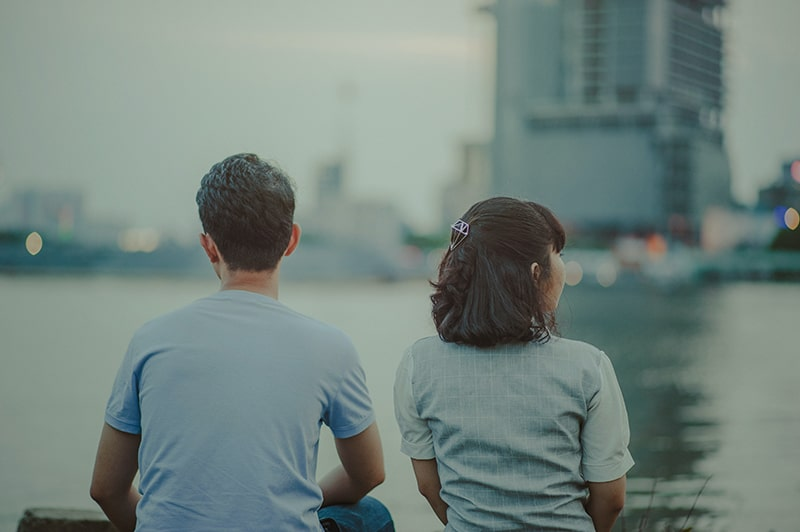 man and woman watching body of water and concrete buildings