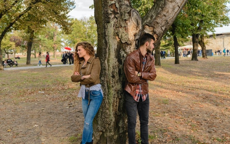 Man and woman wearing leather jackets standing under tree in a park