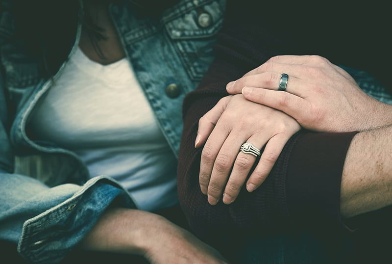 man and woman wearing their silver couple bond ring while holding hands