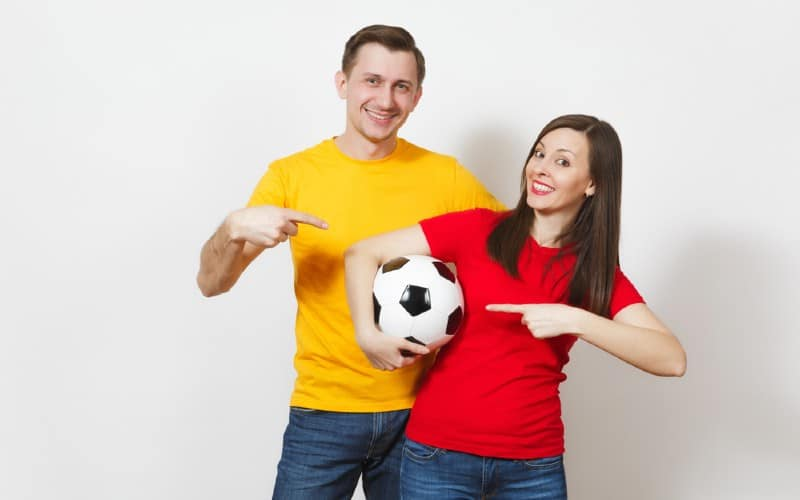Happy man in yellow shirt with woman in red top holding football-ball