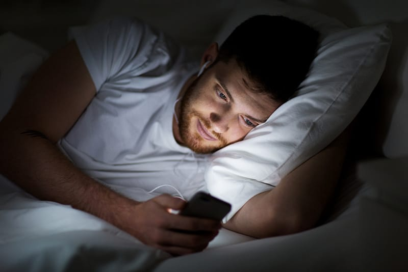 Man in bed with earphones on and using smartphone