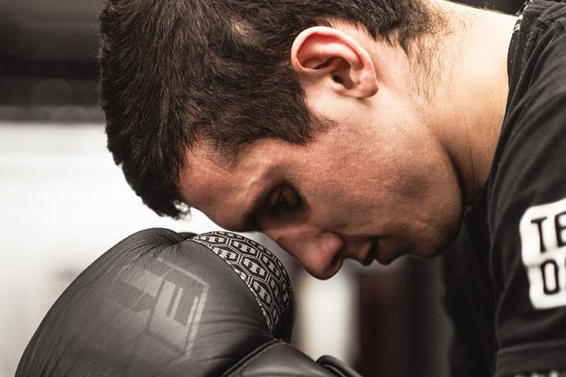 man looking down wearing boxing gloves
