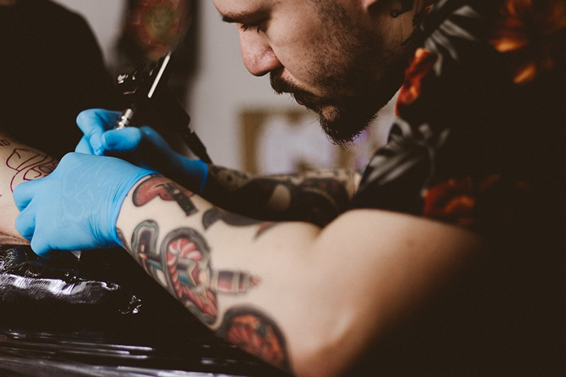 man doing tattoo on person's arm
