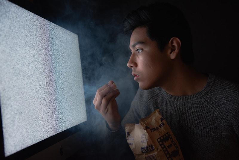 man eating popcorn while staring at tv