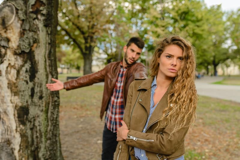 man explaining to a woman in the park wearing brown jackets