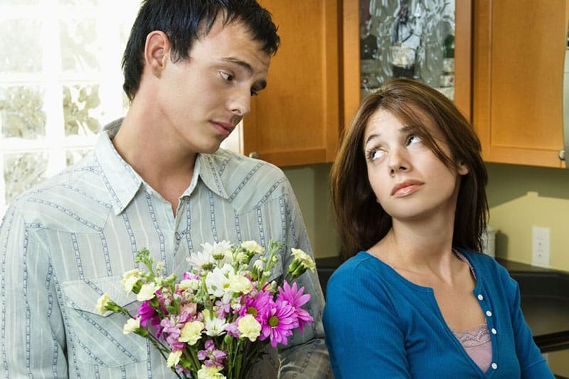 man giving flowers to a woman wearing blue top