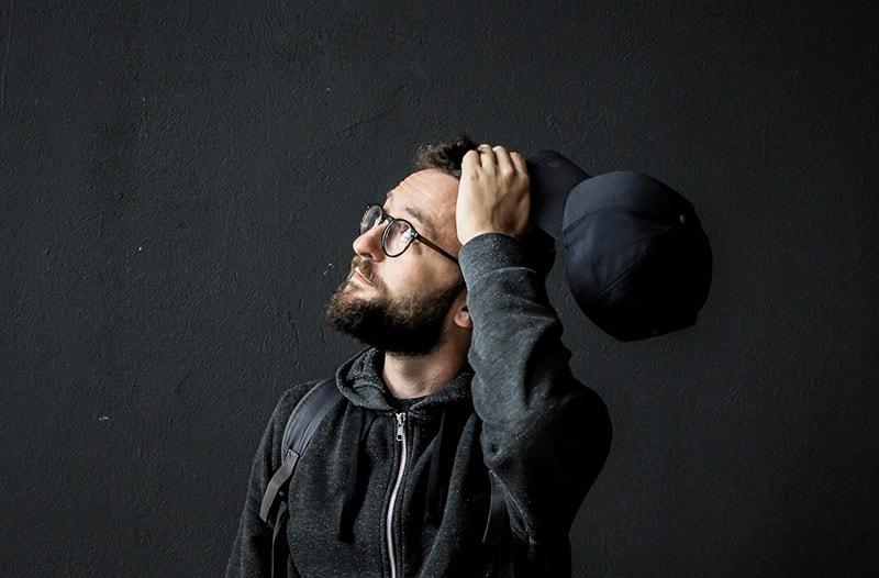 Man wearing hoodie and eyeglasses holding cap