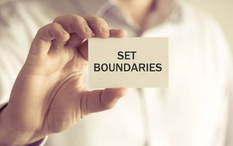 Hamd of a man holding a set boundaries card