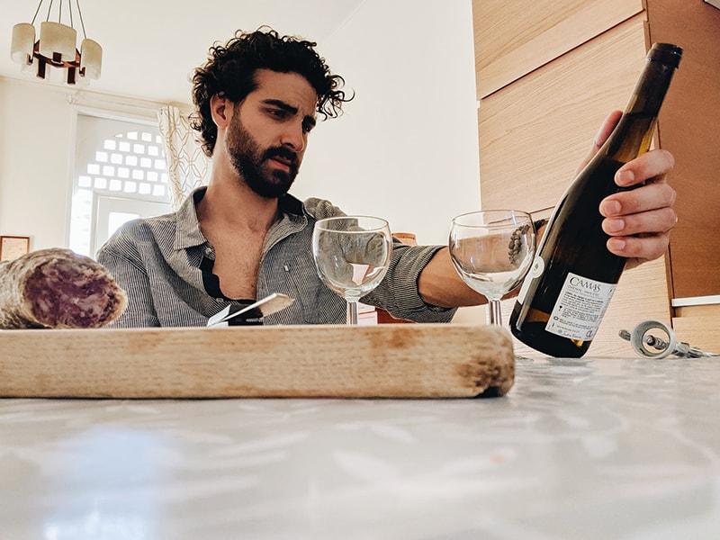 man holding bottle of wine sitting beside table