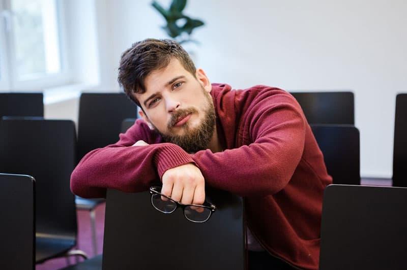 man holding eyeglasses while sittting