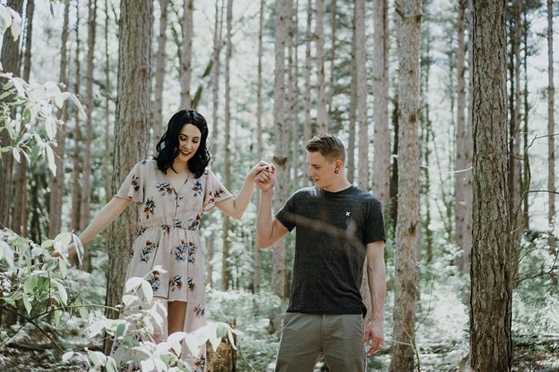 man holding hands with woman in the wood