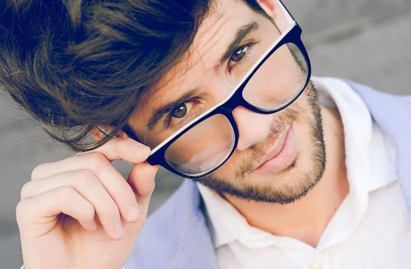 man holding his eyeglasses in formal suit