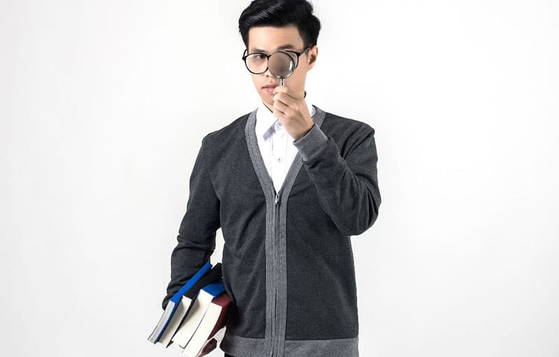 man holding a magnifying glass and books on one hand