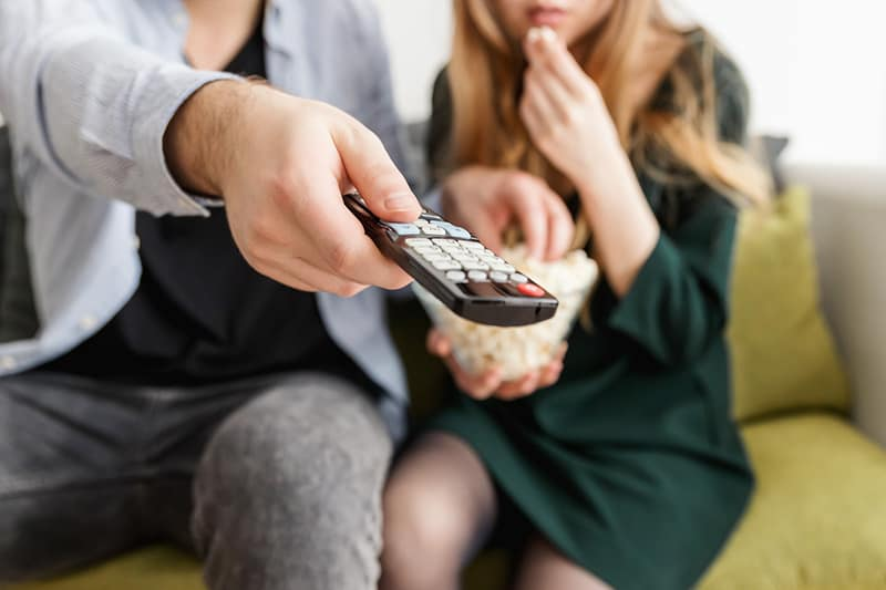 man holding remote control beside woman eating popcorn