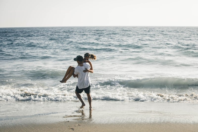 man in white shirt carrying woman on beach