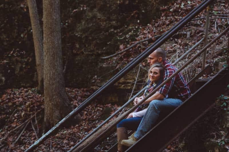 man huggin her girlfriend on staircase during autumn