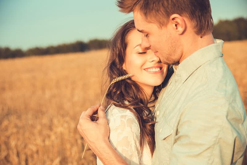 man hugging smiling woman in the field