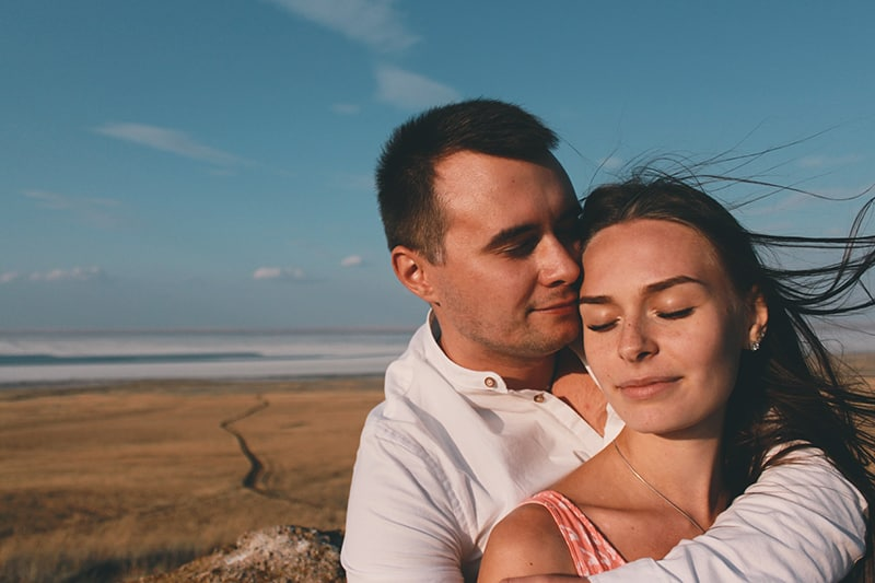 man hugging woman from the back on the seashore