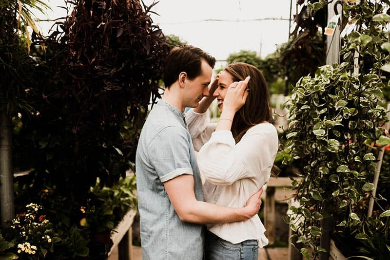 Man and woman hugging surrounded by plants