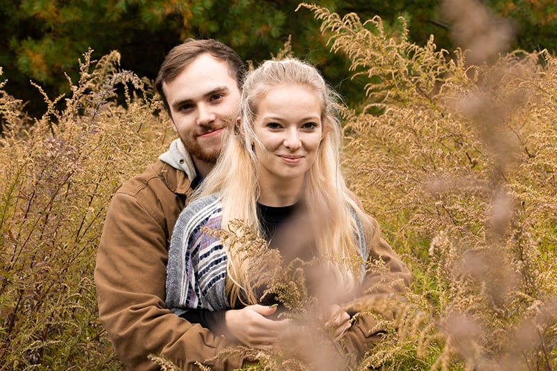 man hugging woman with long blonde hair while sitting in the field