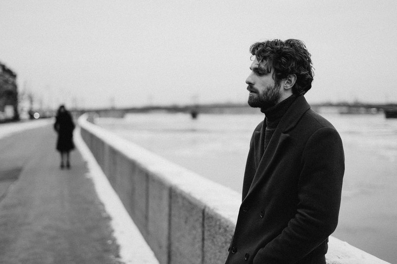 man in black coat leaning on a bridge railings in black and white photography