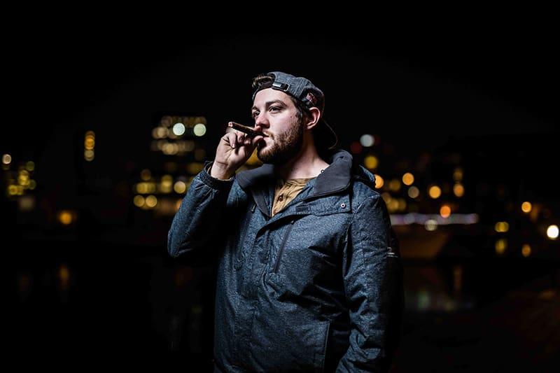 man in black jacket standing while smoking cigar