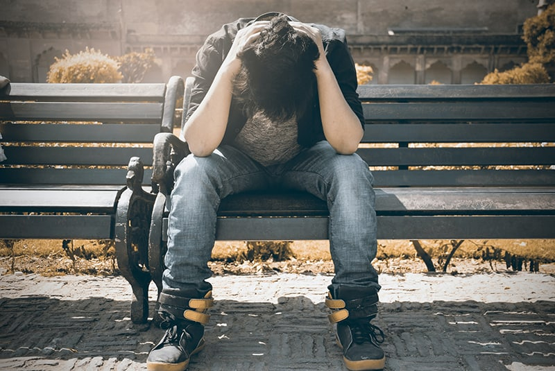 man in black shirt and gray denim pants sitting on the bench