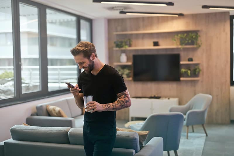 man in black shirt standing and smiling while he looks at phone