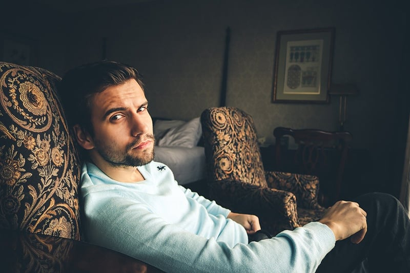 man in blue sweater sitting on the armchair
