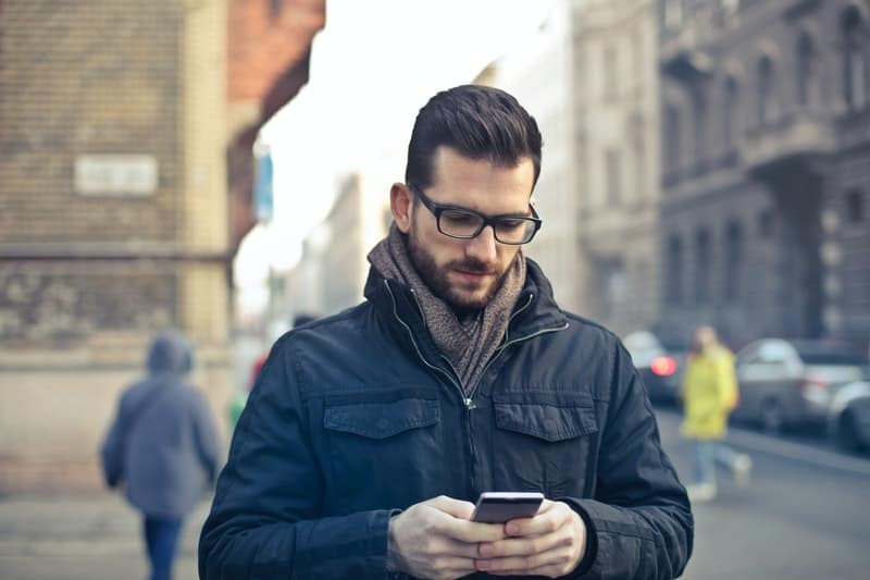 man in eyeglass holding and looking at his cellphone