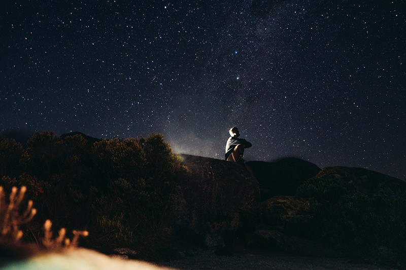 man in white shirt sitting on rock during the nightime