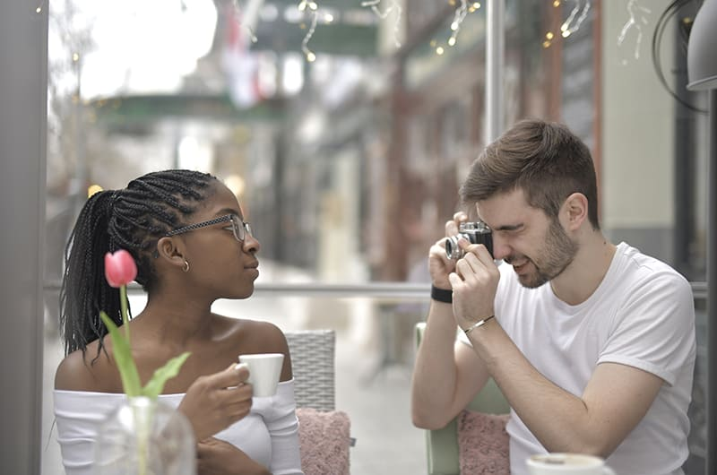man in white t-shirt holding camera and photographing a woman