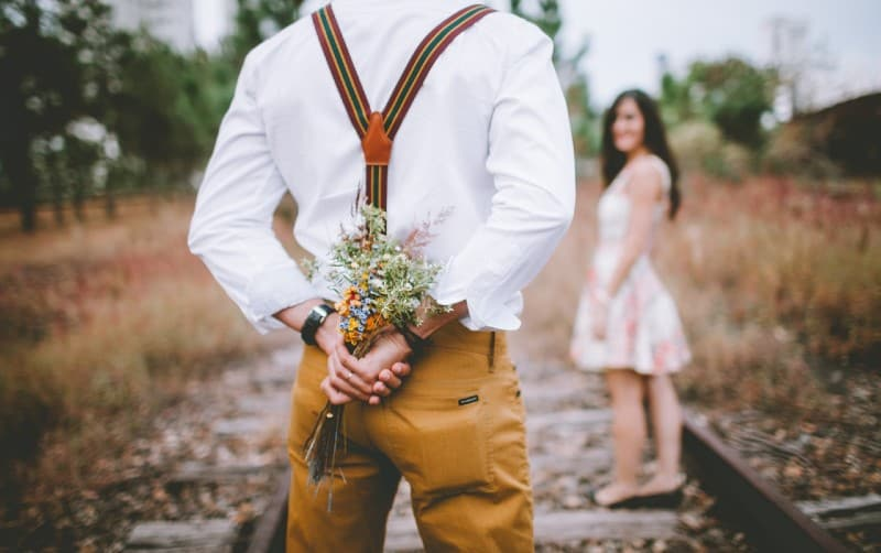 man keeping flowers at his back while looking at a woman
