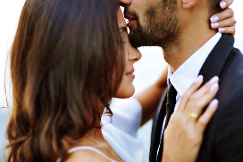 man kissing brunette woman on forehead