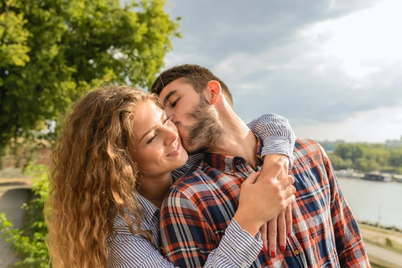 man kissing smiling woman outdoor
