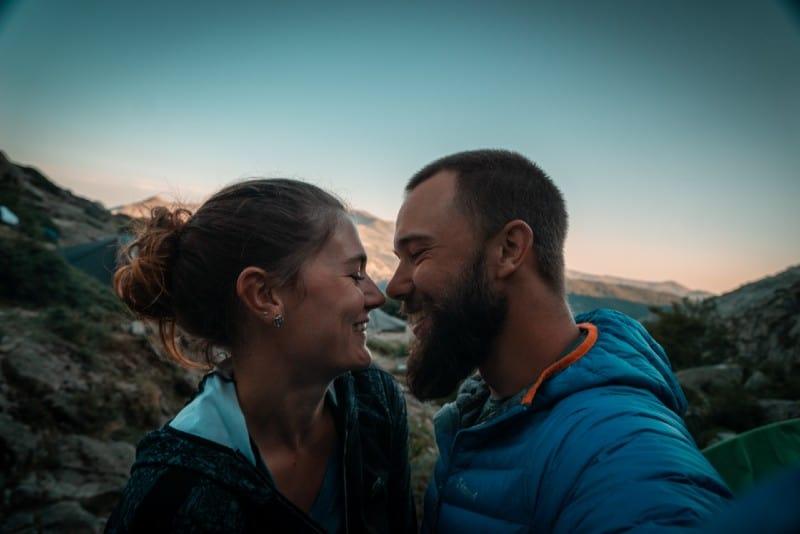 man in blue hoodie kissing woman during daytime