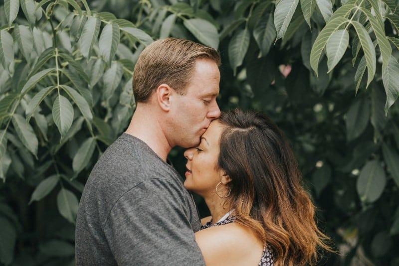 man kissing woman's forehead near tree leaves