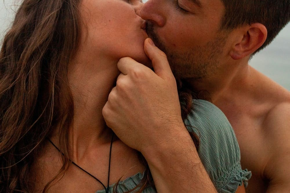 man kissing woman while holding woman's face