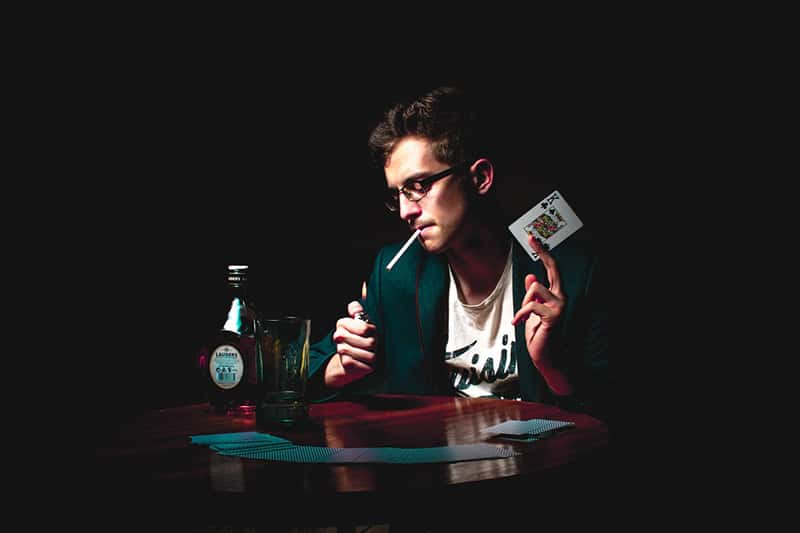 man lightening the cigarette and holding playing card in his hand