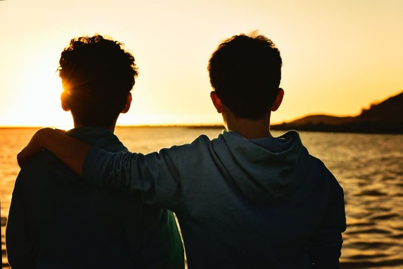 two man looking at water during sunset