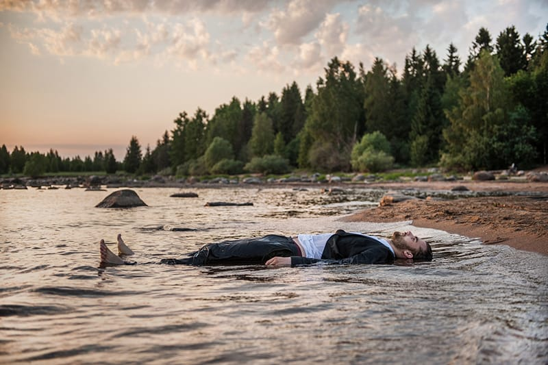 man lying in the river during the sunset