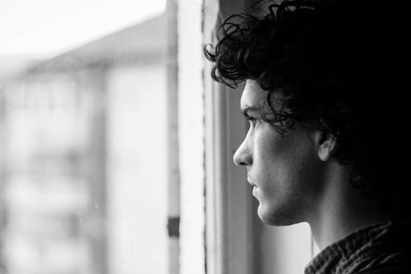 man with curly hair looking through window