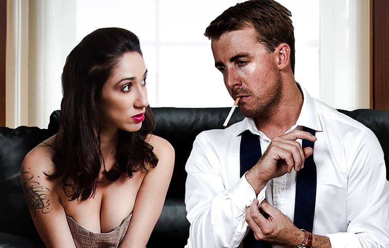 man on cigarette unbuttoning the sleeves beside a woman in dress