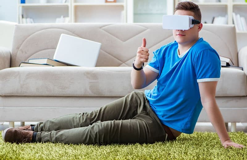 man playing VR sitting on the floor near the sofa