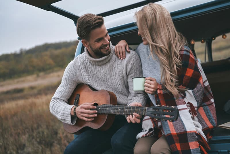 man playing a guitar to his girlfriend