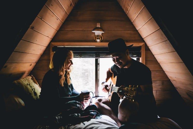 man playing guitar facing woman