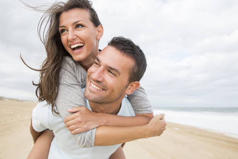 man ridding woman on his back on the beach